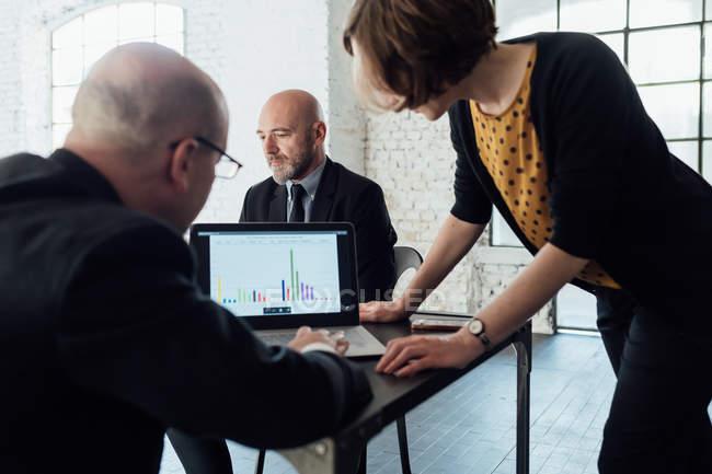 Colegas, olhando para dados gráficos no laptop — Fotografia de Stock