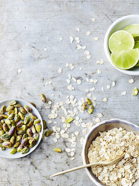 Top view of pistachios, oats and lime on wooden table — Stock Photo