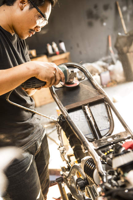 Side view of mechanic working with power tool at custom motorbike shop, Bangkok, Thailand — Stock Photo