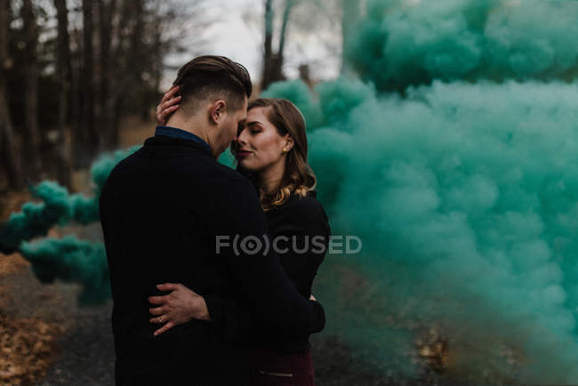 Young couple kissing in forest by green smoke cloud — Stock Photo