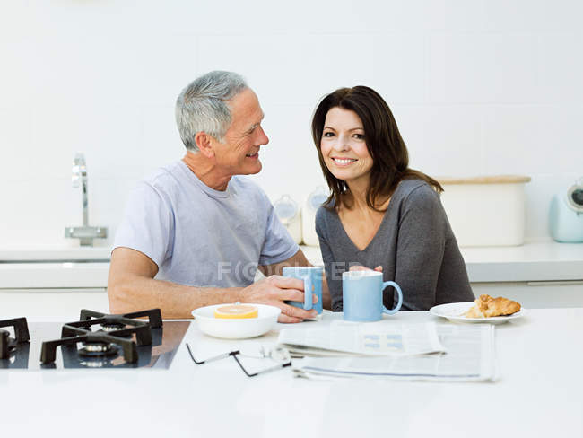 Mature couple having breakfast in kitchen — Stock Photo