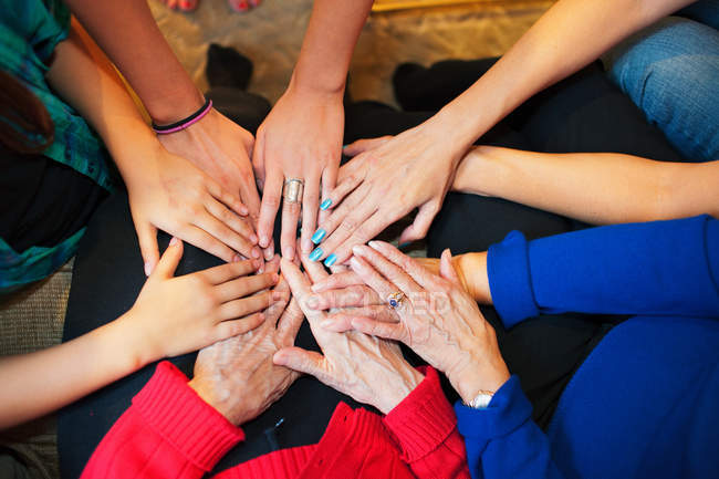 Cropped image of multicultural women putting hands together — Stock Photo