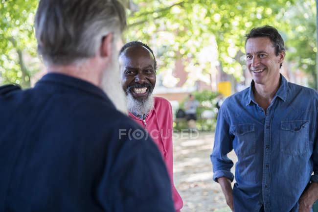 Трое взрослых мужчин разговаривают на улице — стоковое фото