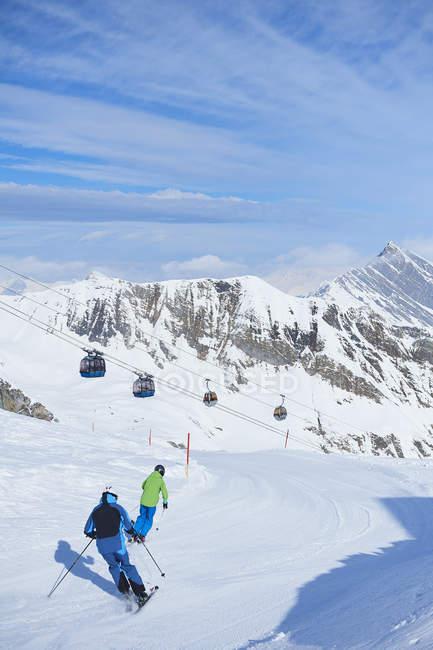Вид сзади отца и сына, Катание на лыжах на трек, Хинтертукс, Тироль, Австрия — стоковое фото