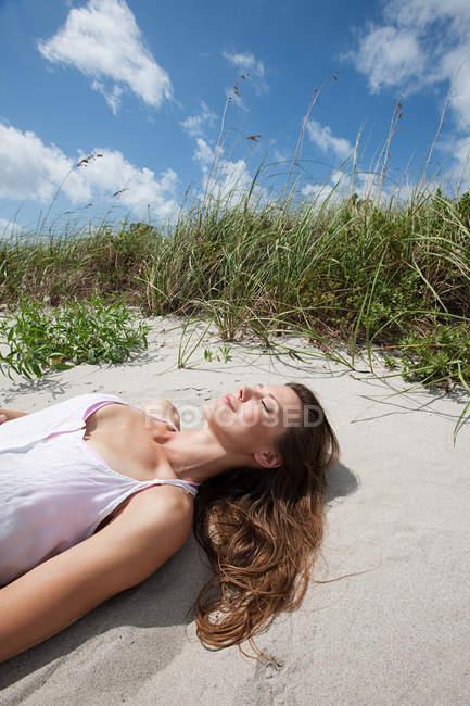 Giovane donna sdraiata addormentata sulla spiaggia — Foto stock