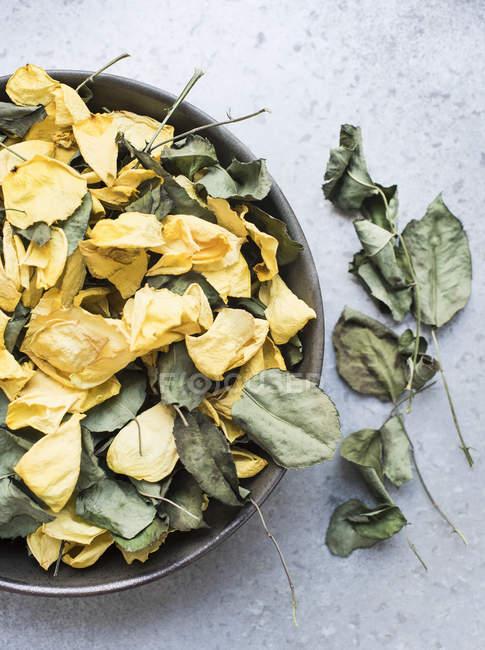 Rosenblätter und trockene Blätter in der Schüssel — Stockfoto