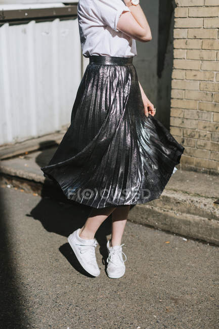 Low section view of Woman in street twirling metallic skirt — Stock Photo