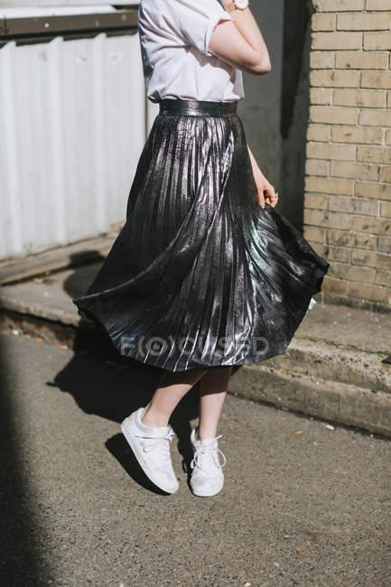 Vue de la section basse de la femme dans la rue tourbillonnant jupe métallique — Photo de stock