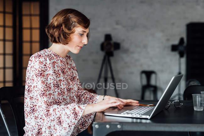 Donna alla scrivania utilizzando il computer portatile in ufficio — Foto stock