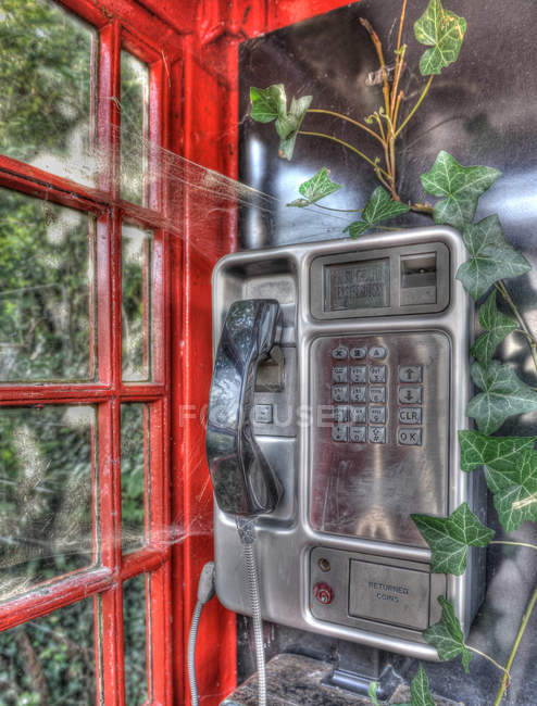 View of old metal phone in red telephone booth — Stock Photo