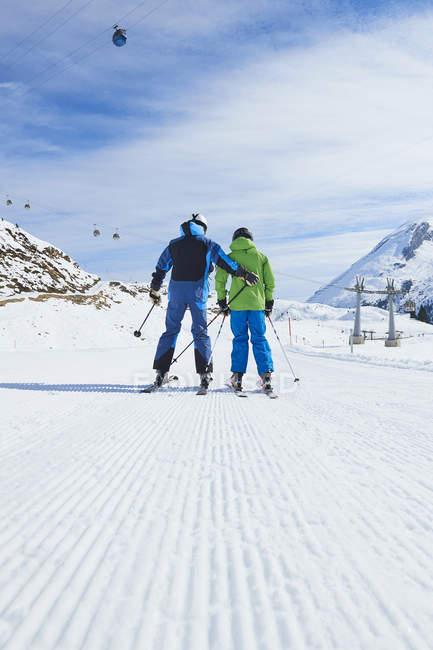 Вид сзади отца и сына на лыжный праздник, Хинтертукс, Тироль, Австрия — стоковое фото