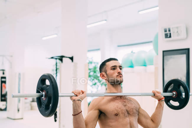 Man weightlifting using barbell in gym — Stock Photo