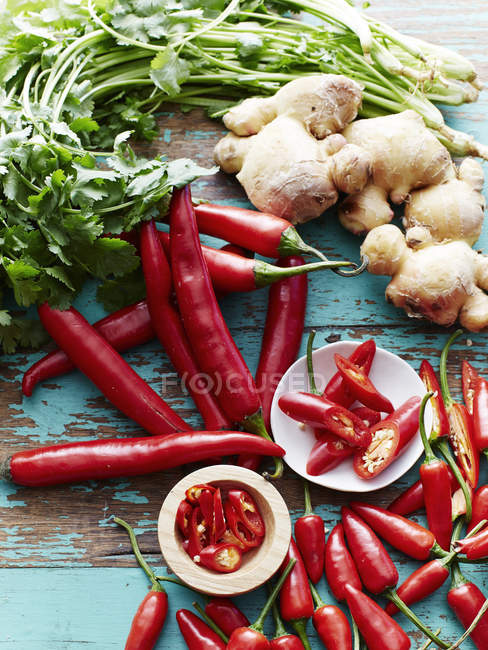 Top view chilli peppers, coriander and ginger on wooden table — Stock Photo