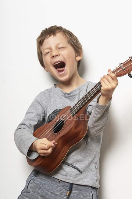 Menino tocando ukulele no fundo branco — Fotografia de Stock