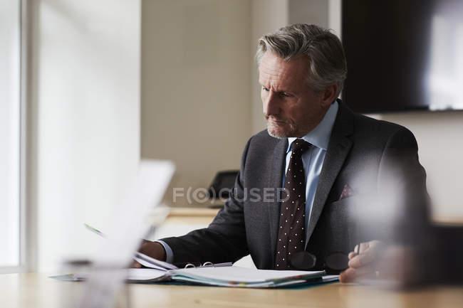 Geschäftsmann im Büro am Schreibtisch beim Blick auf Papierkram — Stockfoto