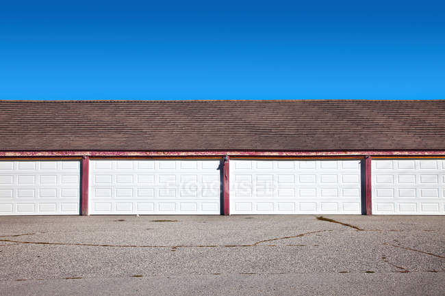 View of row of garages against blue sky — Stock Photo