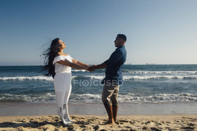 Couple debout sur la plage, main dans la main, face à face — Photo de stock