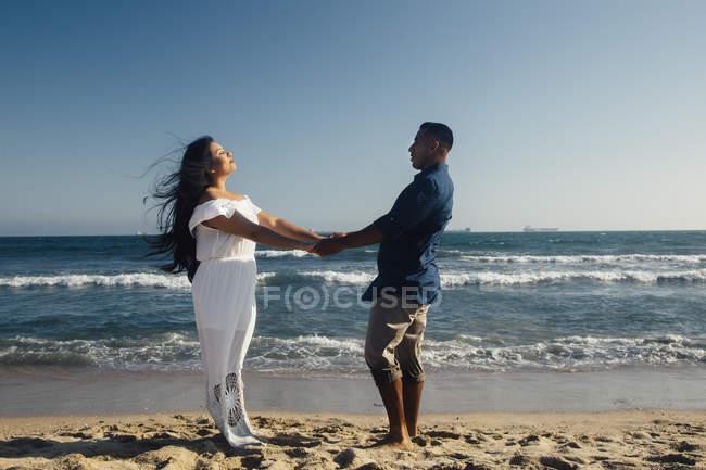 Пара стоит на пляже, взявшись за руки, лицом к лицу — стоковое фото