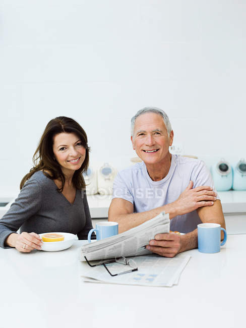Mature couple having breakfast and reading newspaper — Stock Photo