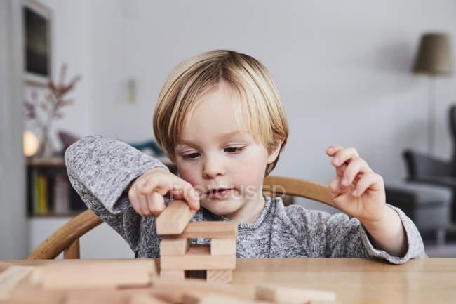 Портрет молодий хлопчик будівлі структури з дерев'яних будівельних блоків — стокове фото