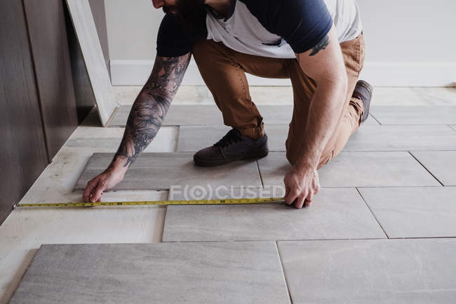 Cropped view of man measuring floor tiles — Stock Photo