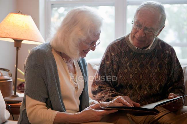 Coppia anziana in cerca di album fotografico — Foto stock