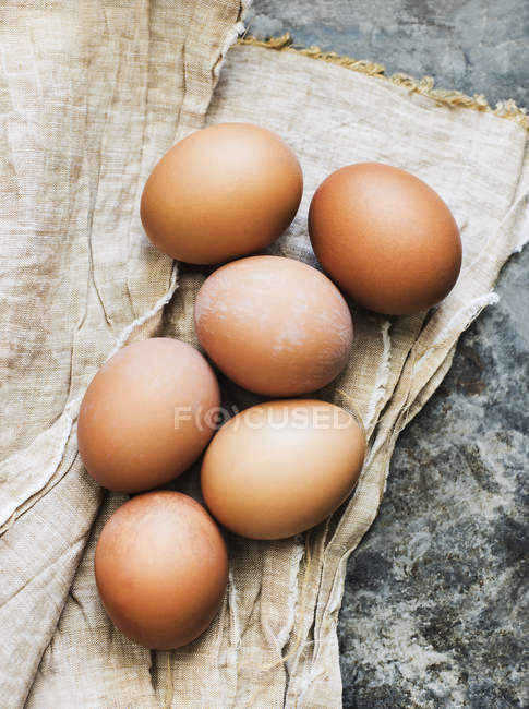 Close-up view of six fresh brown eggs on a cloth — Stock Photo