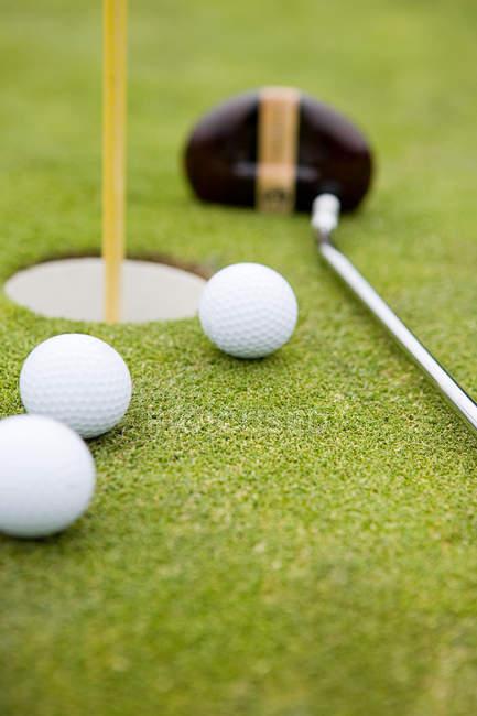Golfbälle und golf-Loch, Nahaufnahme — Stockfoto