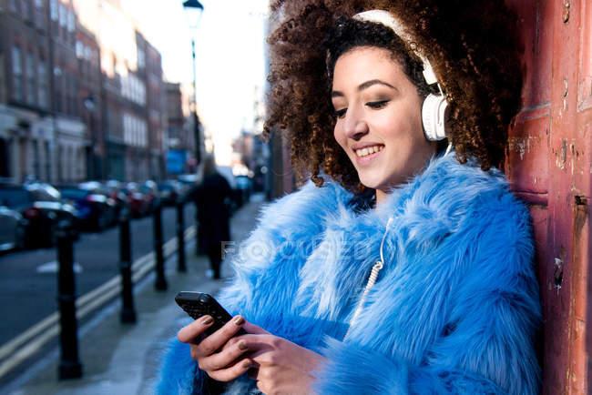 Ritratto di donna in strada che ascolta musica attraverso le cuffie su smartphone — Foto stock