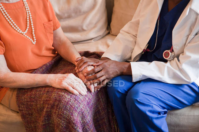 Doctor in blue medical form comforting patient — Stock Photo