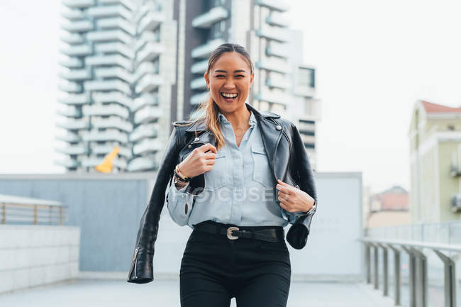 Portrait of businesswoman wearing leather jacket around shoulders — Stock Photo