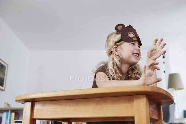 Young girl at table wearing bear mask — Stock Photo