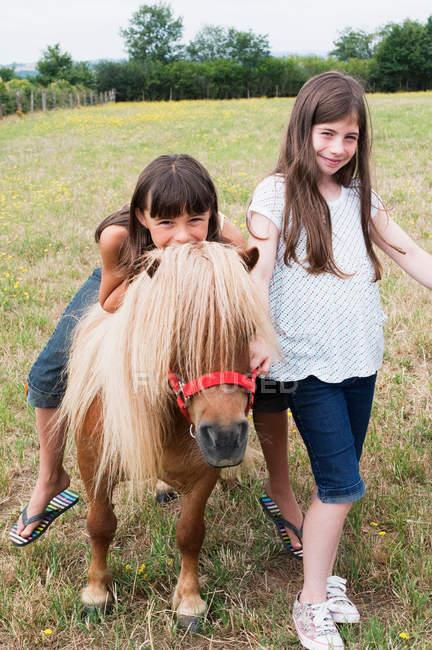 Retrato de dos chicas con pony en el campo - foto de stock