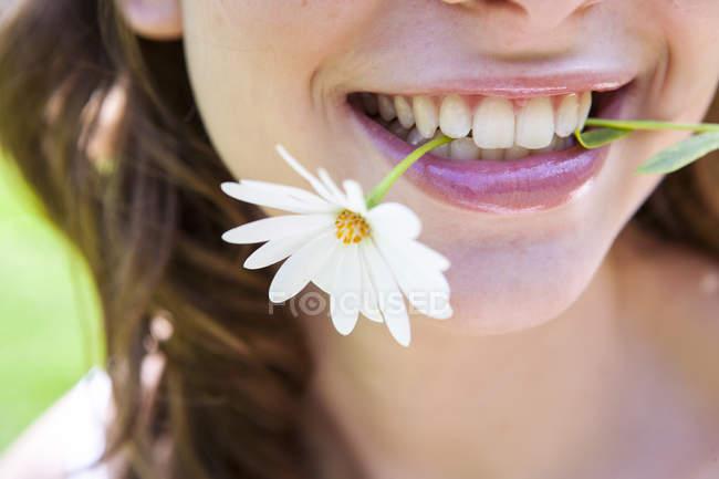 Close up de mulher sorrindo com margarida nos dentes — Fotografia de Stock