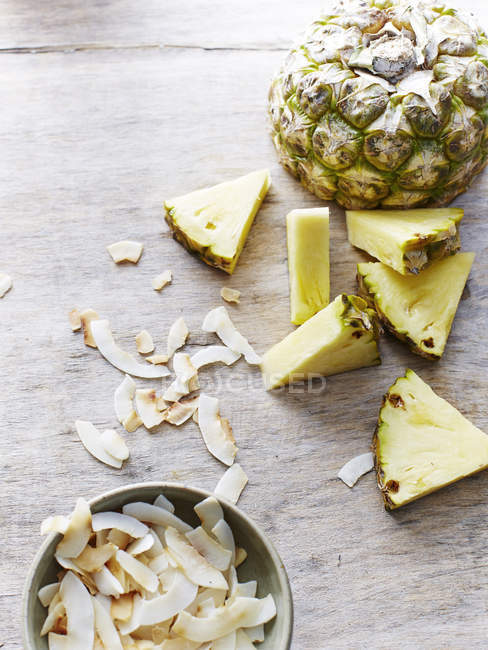 Top view of fresh ripe pineapple, coconut slices on table — Stock Photo