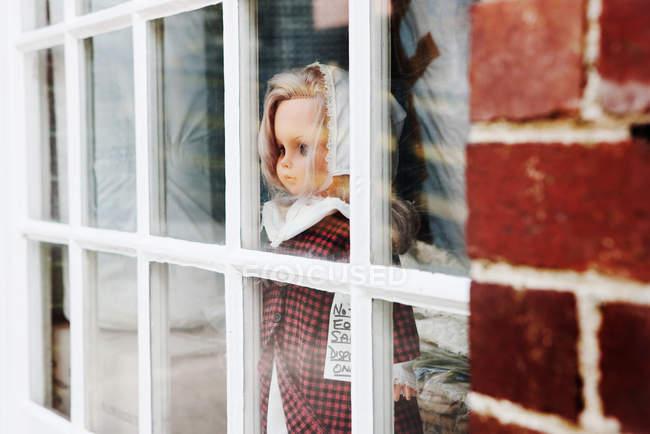 Puppe schaut aus dem Fenster, Nahaufnahme — Stockfoto