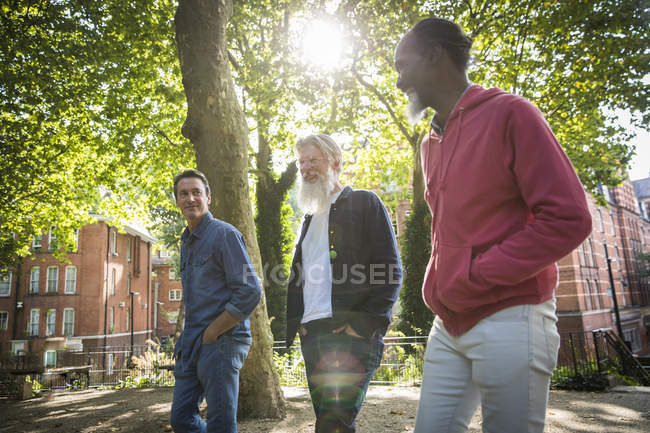 Three mature men walking on city street — Stock Photo