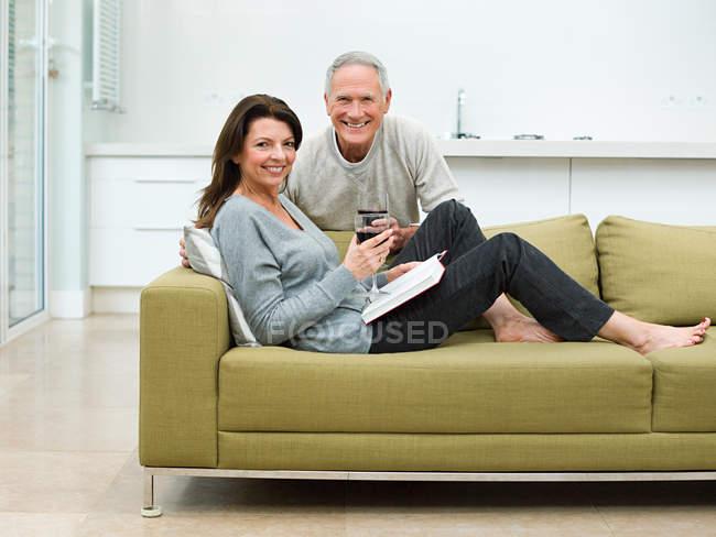 Mature couple sitting on sofa with wine — Stock Photo
