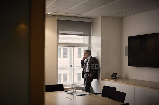 Businessman in office making telephone call on smartphone — Stock Photo