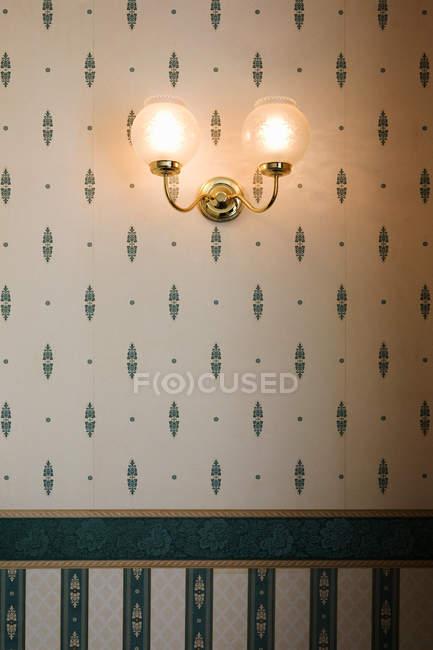 Настенный светильник с узорными обоями — стоковое фото