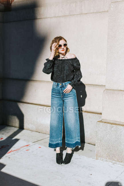 Portrait of woman wearing flared jeans looking away, full length — Stock Photo