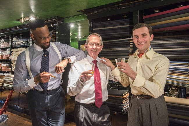 Tailors celebrating in traditional tailors shop — Stock Photo