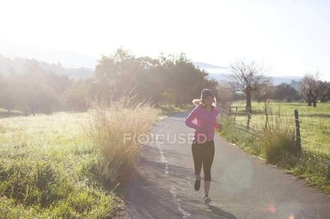 Giovane donna che corre lungo la strada rurale — Foto stock