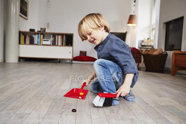 Niño jugando con el polvo de juguete y cepillo - foto de stock
