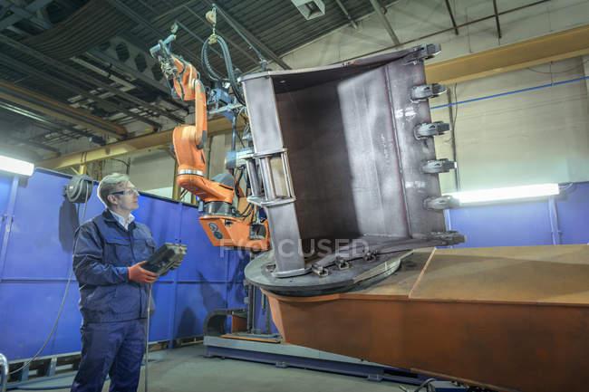 Инженер с контроллером роботизированного сварочного цеха на машиностроительном заводе — стоковое фото
