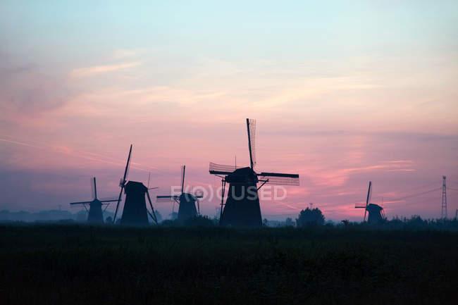 Силуэты ветряные мельницы на идиллическом закат в Нидерланды — стоковое фото