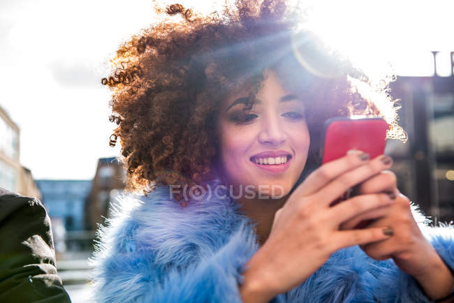 Portrait of woman with afro looking at smartphone — Stock Photo