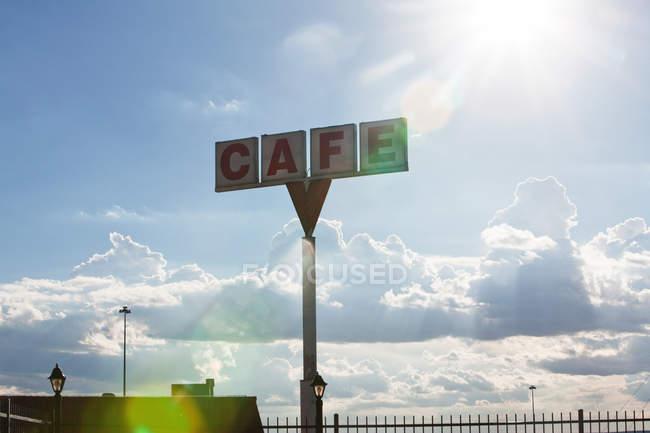 Café Zeichen gegen Himmel mit Wolken mit Lens-flares — Stockfoto