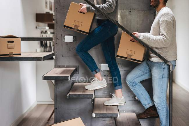 Couple carrying cardboard boxes up stairs — Stock Photo
