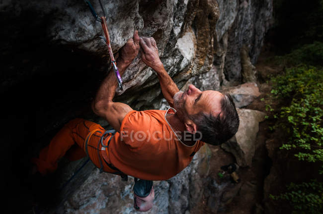 Low angle view of man rock climbing, Hidden Valley, Cat Ba Island, Vietnam — Stock Photo